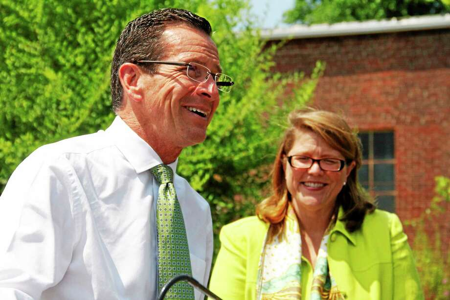 Gov. Dannel Malloy laughs as Winsted Mayor Marsha Sterling looks on in the background during a brief press conference announcing a $500,000 grant to help redevelop a site in the town on Friday in Winsted. Winsted was one of several municipalities in Litchfield County to receive the Small Town Economic Assistant Program grants. Photo: Esteban L. Hernandez — Register Citizen