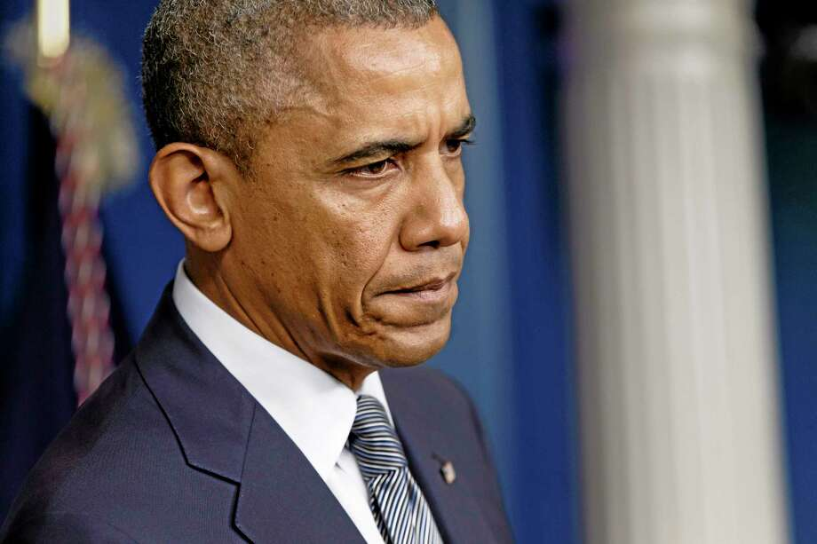 President Barack Obama pauses while speaking about the situation in Ukraine, Friday, July 18, 2014, in the Brady Press Briefing Room of the White House in Washington. The president said one American was killed on the plane over Ukraine, and the airliner was shot down by a surface-to-air missile in an area controlled by Russian-backed separatists. (AP Photo/J. Scott Applewhite) Photo: AP / AP