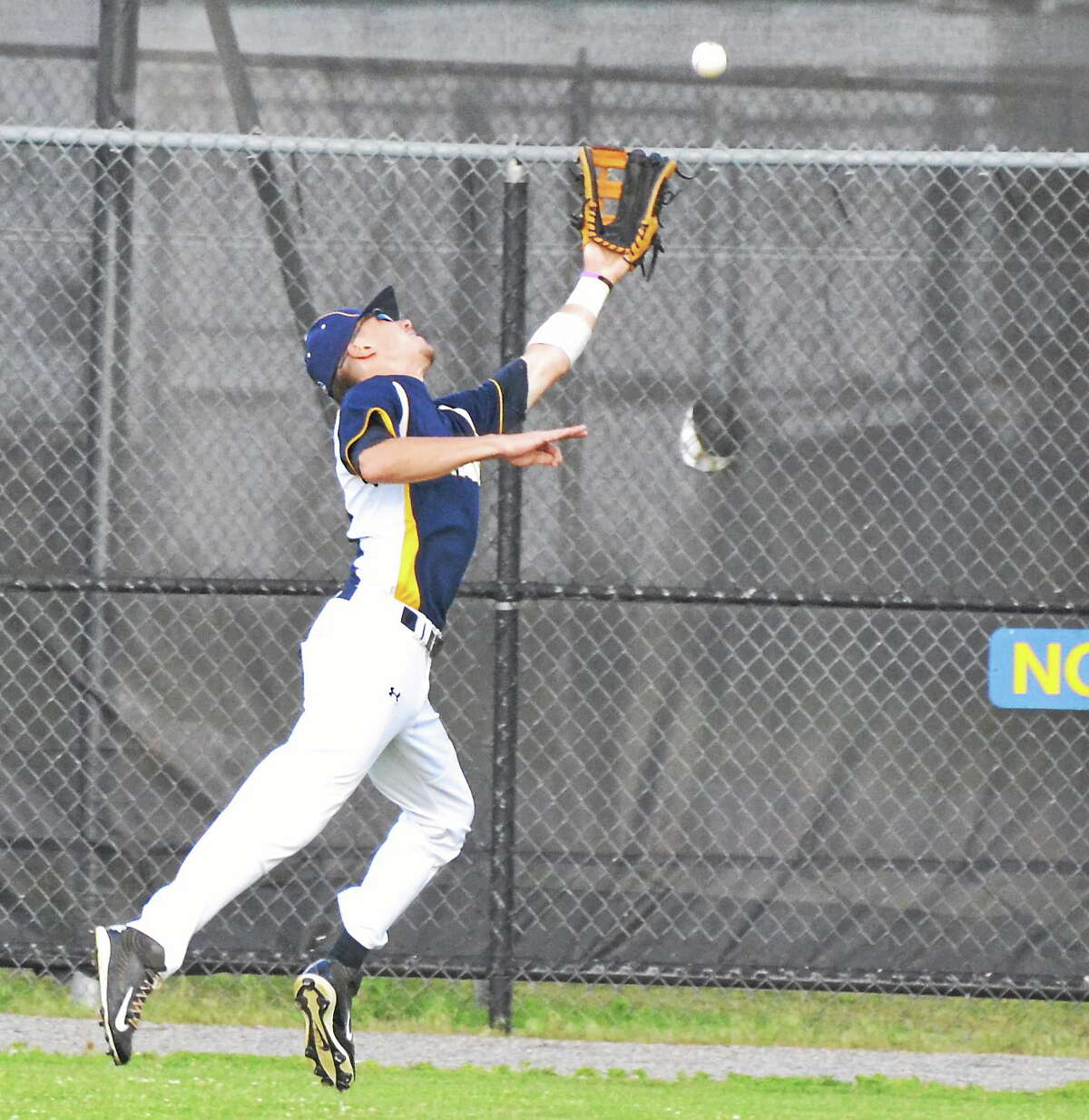 Torrington Titans' center fielder Chris Scura reaches out to try and catch a deep fly ball, but the ball would drop in over his head.