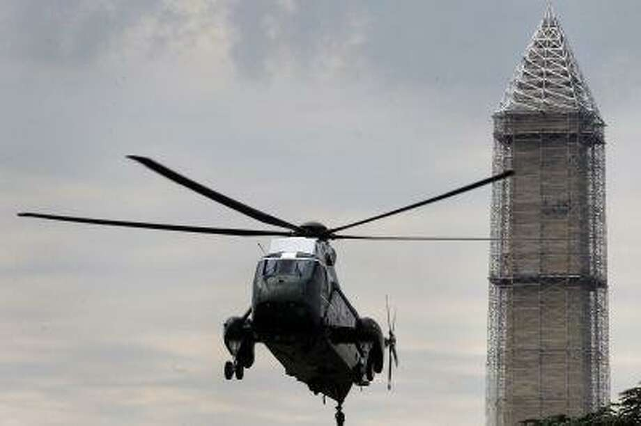 In this photo taken May 28, 2013, repairs continue on the Washington Monument as Marine One helicopter comes in for a landing on the South Lawn of the White House in Washington. While the Monument's earthquake damage is being repaired over the next year, 488 lamps will restore the tower's glow each night on the National Mall starting Monday, July 8, 2013. (AP Photo/Charles Dharapak) Photo: AP / AP