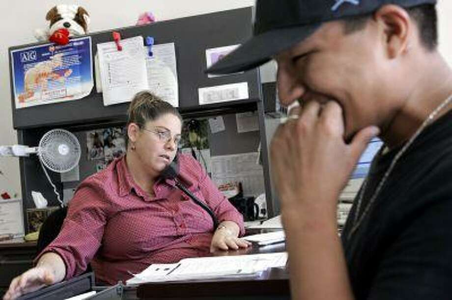 Ayesha Tully, left, responds to call while Larryll Emerson, 20, waits for information pertaining to his next work assignment Tuesday, from the Staffmark temp agency in Cypress, Calif. (AP Photo/Ric Francis) Photo: ASSOCIATED PRESS / AP2005