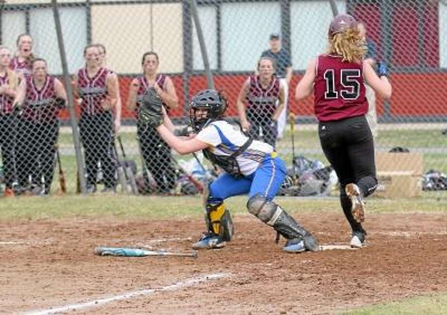 Marianne Killacky/Special to Register Citizen  As her teammates cheer her on, Brittany Anderson (15) crosses home plate for the Lady Raiders' first run on a sacrifice bunt by teammate Marissa Morris. / 2013