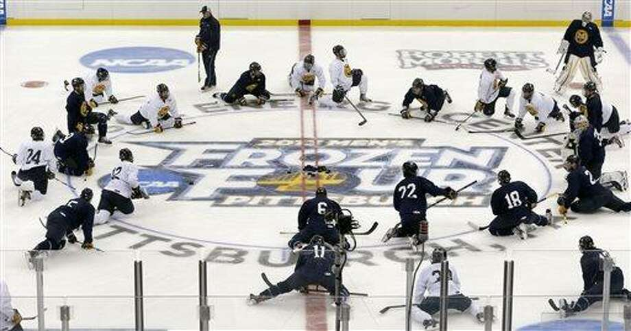 Quinnipiac players stretch at center ice during NCAA college hockey practice at the Consol Energy Center, Wednesday, April 10, 2013, in Pittsburgh. Quinnipiac is scheduled to play St. Cloud State in a semifinal at the Frozen Four on Thursday. (AP Photo/Keith Srakocic) Photo: ASSOCIATED PRESS / AP2013
