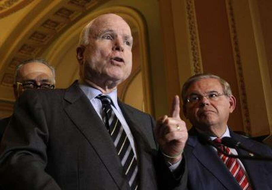 U.S. Senator John McCain (R-AZ) speaks to the media next to Senate Foreign Relations Committee Chairman Robert Menendez (D-NJ) after the Senate passed the immigration bill on Capitol Hill in Washington June 27, 2013. Photo: REUTERS / X00866