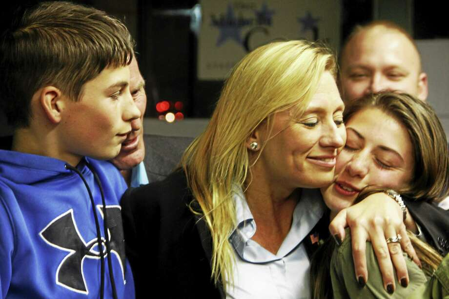 State Rep. Michelle Cook, D-65, embraces her daughter, Ashlynn, while her son, Billy, looks on after unofficial numbers showed her being re-elected to the General Assembly Tuesday, Nov. 4, in Torrington. Her opponent, Dan Farley, did not concede the race by press time Tuesday as he was waiting for votes to be certified. Photo: Esteban L. Hernandez — The Register Citizen