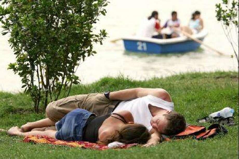 Dream on: a couple snoozes in Madrid's Retiro Garden.