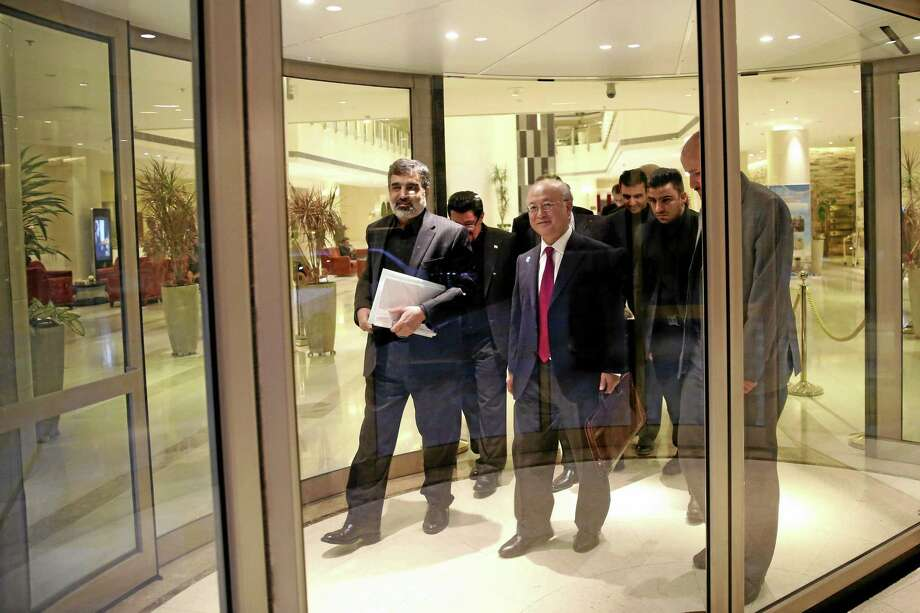 International Atomic Energy Agency (IAEA) Director General Yukiya Amano, center, leaves the Azadi Hotel after briefing reporters on the progress of nuclear negotiations with Iranian officials in Tehran, Iran, Monday, Nov. 11, 2013. Iran and the U.N. nuclear watchdog agency have reached a roadmap deal for cooperation during talks in Tehran Saturday that expands the monitoring of the country's nuclear sites. (AP Photo/Ebrahim Noroozi) Photo: AP / AP
