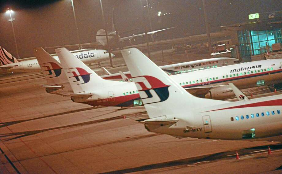 Malaysia Airlines planes are parked at Kuala Lumpur International Airport in Sepang, Malaysia, Thursday, July 18, 2013.  A Malaysia Airlines flight with nearly 300 people aboard crashed over eastern Ukraine near the Russian border on Thursday, the Ukraine government and a regional European aviation official reported, Thursday, and the Interfax news agency said it had been shot down.(AP Photo/Joshua Paul) Photo: AP / AP
