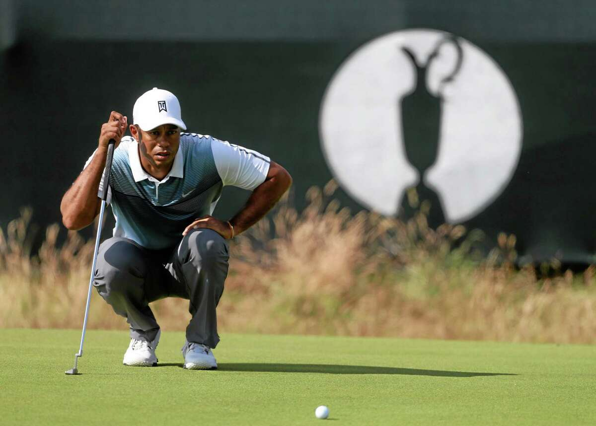 Tiger Woods lines up a putt on the third green during the first day of the British Open Thursday at the Royal Liverpool golf club in Hoylake, England.