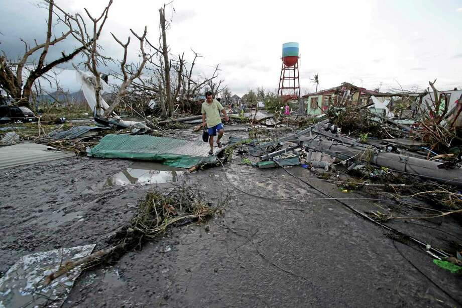 """A resident walks by toppled trees and electric posts after powerful Typhoon Haiyan slammed into Tacloban city, Leyte province, central Philippines on Saturday, Nov. 9, 2013. The central Philippine city of Tacloban was in ruins Saturday, a day after being ravaged by one of the strongest typhoons on record, as horrified residents spoke of storm surges as high as trees and authorities said they were expecting a """"very high number of fatalities."""" (AP Photo/Aaron Favila) Photo: AP / AP"""