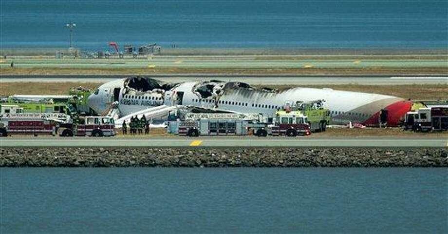Fire crews respond to the scene where Asiana Flight 214 crashed at San Francisco International Airport on Saturday, July 6, 2013, in San Francisco. (AP Photo/Noah Berger) Photo: AP / FR34727 AP