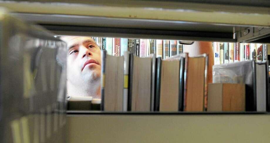 Patrick Jordan shelves books at the West Hartford Public Library. Photo: Mara Lavitt — New Haven Register    / Mara Lavitt