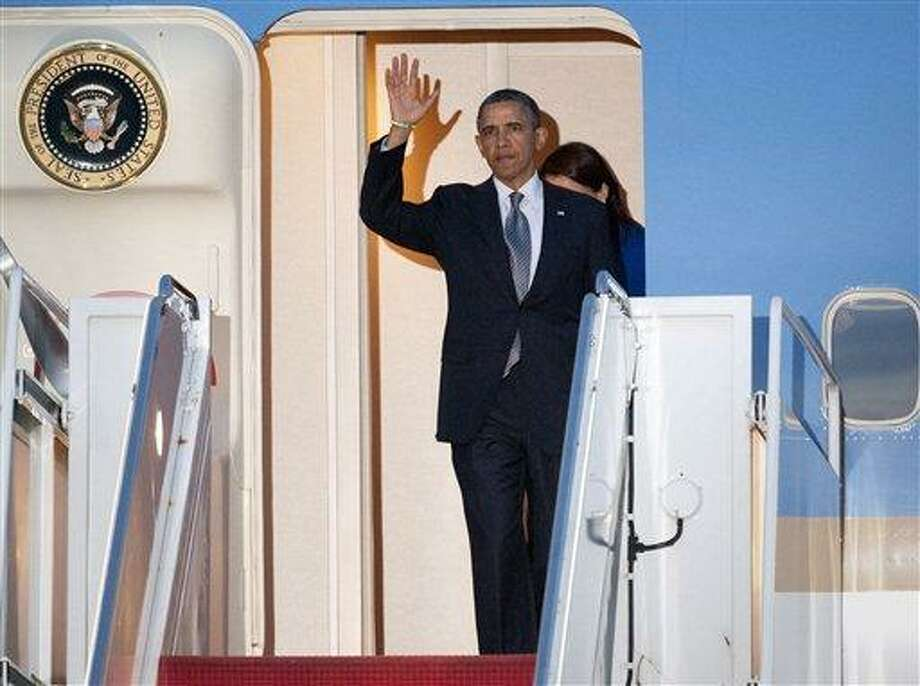 President Barack Obama waves from the doorway of Air Force One at Andrews Air Force Base, Md., Monday, April 8, 2013 before he exited the airplane with families who lost relatives in the Sandy Hook Elementary School shooting in Newtown, Conn., in December 2012. Obama was returning from Hartford, Conn., where he spoke at the University of Hartford, near the state capitol where last week the governor signed into law some of the nation's strictest gun control laws. . (AP Photo/Cliff Owen) Photo: AP / FR170079 AP