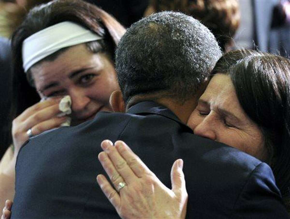 President Barack Obama hugs Newtown, Conn., family members after speaking at the University of Hartford in Hartford, Conn., Monday, April 8, 2013. Obama said that lawmakers have an obligation to the children killed and other victims of gun violence to act on his proposals. (AP Photo/Susan Walsh)