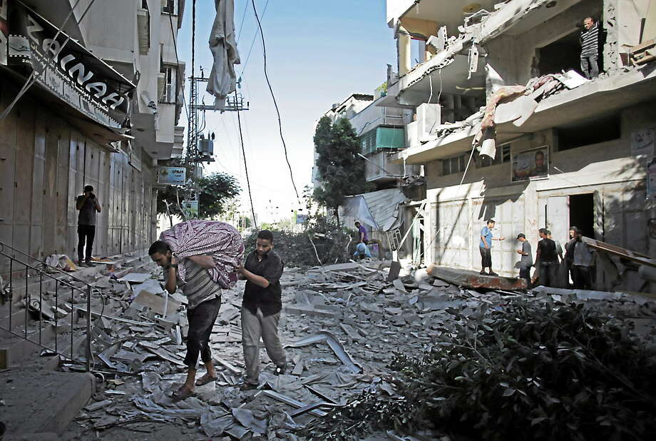 Palestinians salvage what they can of their belongings from the rubble of their destroyed house following an early morning Israeli missile strike in Gaza City on July 16, 2014. Photo: AP Photo/Khalil Hamra  / AP
