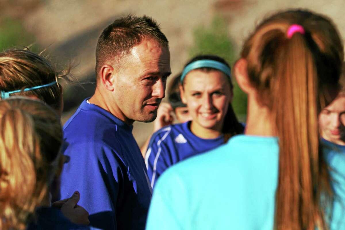 Lewis Mills girls soccer head coach Dennis Fowler talks to his team during practice last week.