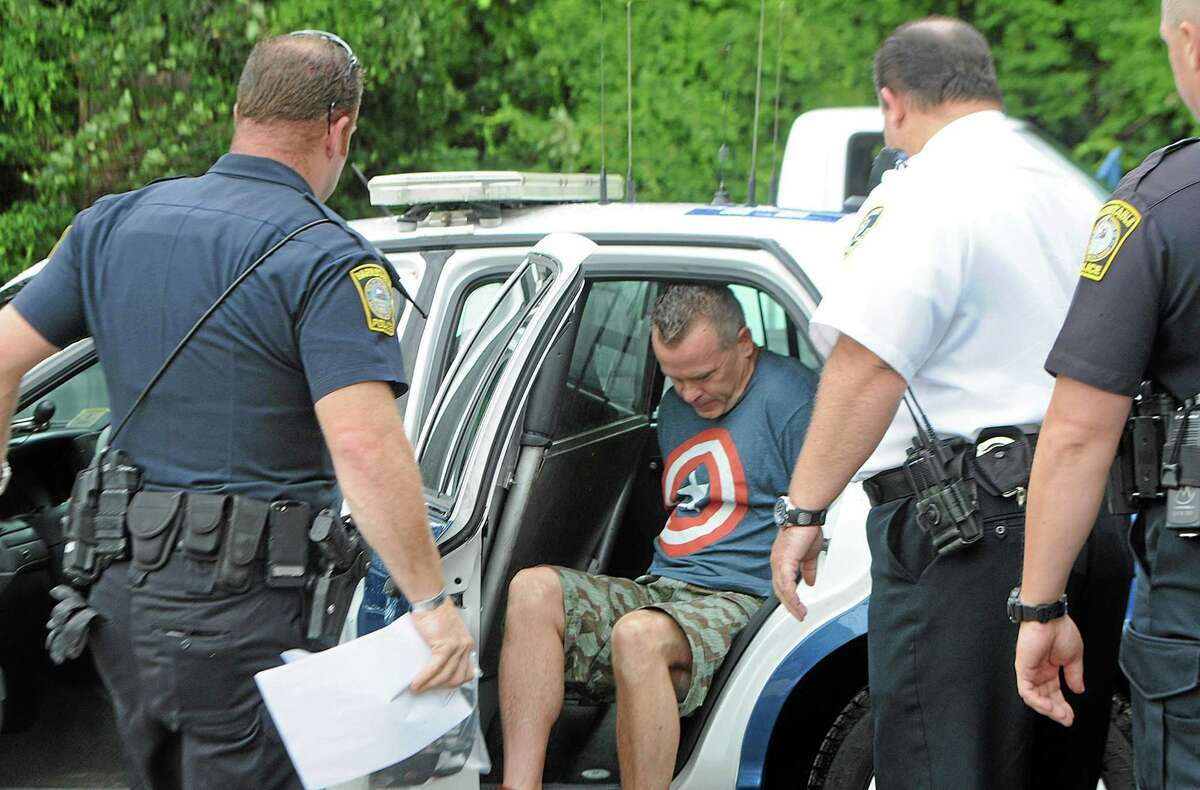 James Lacroix, 53, is led from a police cruiser into Barnstable District Court in Barnstable, Mass. Wednesday, July 16, 2014. Lacroix, accused of breaking into a home once owned by John F. Kennedy, told authorities he was looking for singer Katy Perry. (AP Photo/Cape Cod Times, Steve Heaslip)