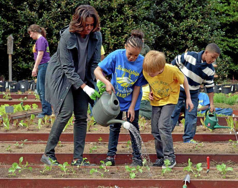 This April 2 file photo shows first lady Michelle Obama helping to hold a watering can after she and Friendship Public Charter Elementary School student Dynasty Meade, center, and Bancroft Elementary School student Silas Stutz, right, planted broccoli in the White House Kitchen Garden. Michelle Obama has made an effort to get kids to stay active and eat healthy across the country. Photo: AP File Photo  / AP