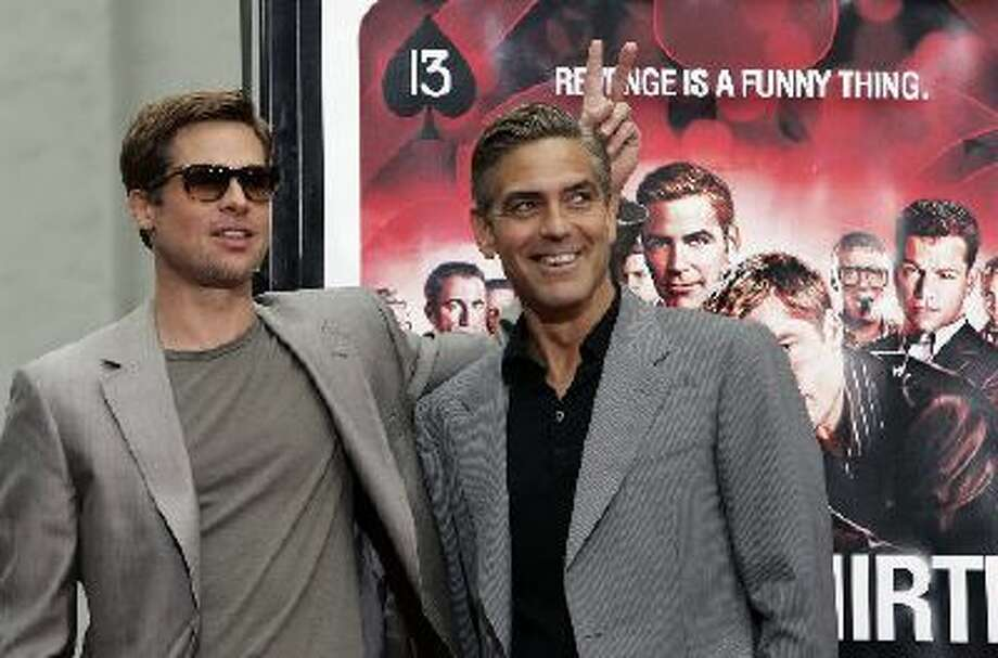 """Actor Brad Pitt jokes around with his co-star George Clooney during a ceremony placing their hands in cement as part of the """"Ocean's 13"""" movie promotion, Tuesday June 5, 2007 outside Grauman's Chinese Theatre in Los Angeles."""