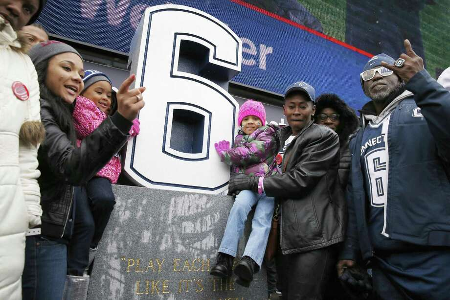 Relatives of former UConn player Jasper Howard, including step-father Herny Williams, right, grandmother Vicki Ross, second from right, mother Joangila Howard, third from right, and fiancée Daneisha Freeman, second from left, gather around a memorial to Howard after its unveiling during halftime of the Huskies' 37-29 win over Central Florida on Saturday at Rentschler Field in East Hartford. Photo: Michael Dwyer — The Associated Press  / AP