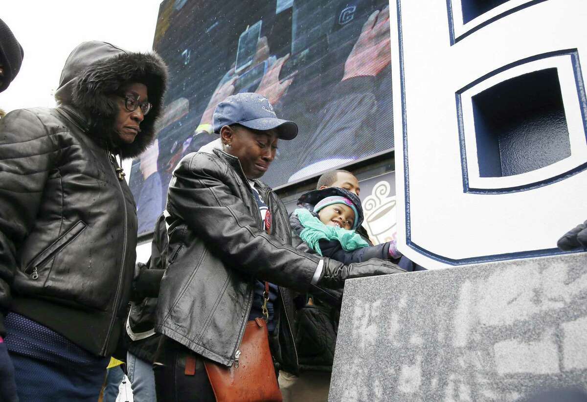Former UConn player Jasper Howard's mother, Joangila Howard, second from left, and his grandmother Vicki Ross, left, bow their heads after the unveiling of a memorial to Jasper during halftime of the Huskies' 37-29 win over Central Florida on Saturday at Rentschler Field in East Hartford.