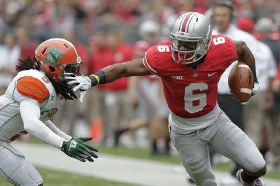 In this Sept. 21, 2013 file photo, Ohio State wide receiver Evan Spencer (6) avoids a Florida A&M defender during a game in Columbus, Ohio.