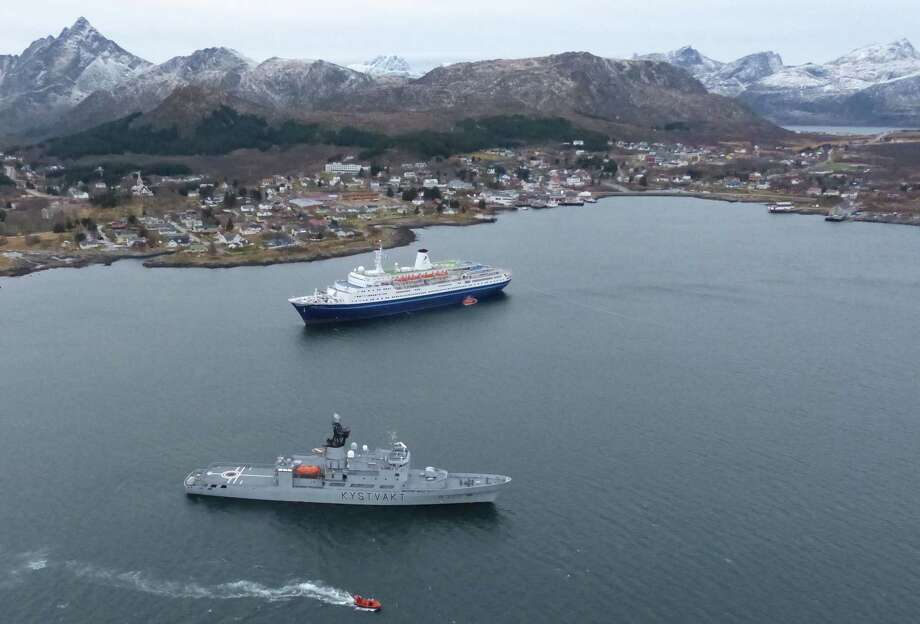 """This image made available by the Royal Norwegian Air Force taken from a rescue helicopter shows a Norwegian coast guard vessel in front of the  Bahamas-registered cruise liner """"Marco Polo"""" aground near Gravdal in northern Norway, Saturday Nov. 1, 2014. Passengers had been allowed to leave the cruise ship, which was carrying more than a thousand people when it ran aground in the Lofoten archipelago early Saturday. The same liner also ran aground briefly in a nearby archipelago in March, according to Norwegian media. The cause of that incident remained unclear. (AP Photo/Royal Norwegian Air Force) NORWAY OUT Photo: AP / Royal Norwegian Air Force"""