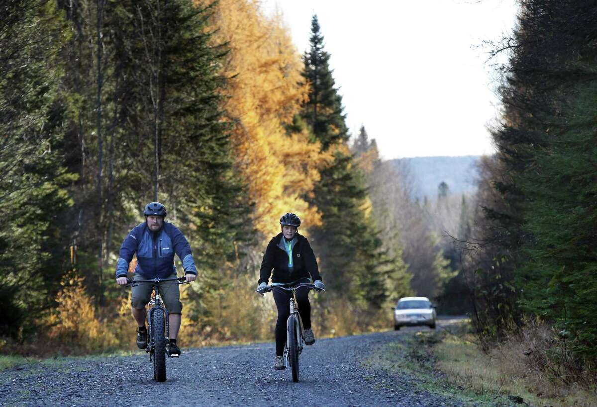 Nurse Kaci Hickox, right, and her boyfriend, Ted Wilbur are followed by a Maine State Trooper as they ride bikes on a trail near their home in Fort Kent, Maine, Thursday, Oct. 30, 2014. State officials are going to court to keep Hickox in quarantine for the remainder of the 21-day incubation period for Ebola that ends on Nov. 10. Police are monitoring her, but can't detain her without a court order signed by a judge.( AP Photo/Robert F. Bukaty)