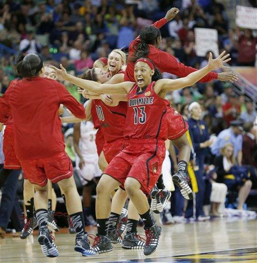 Louisville players including Cortnee Walton (13) celebrate after a national semifinal against California at the Women's Final Four of the NCAA college basketball tournament, Sunday, April 7, 2013, in New Orleans. Louisville won 64-57. (AP Photo/Dave Martin) Photo: AP / AP