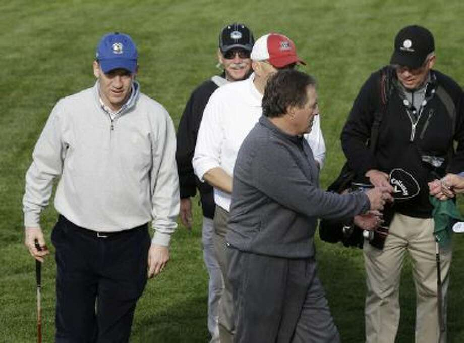 Peyton Manning and Bill Belichick approach the fifth green of Pebble Beach.