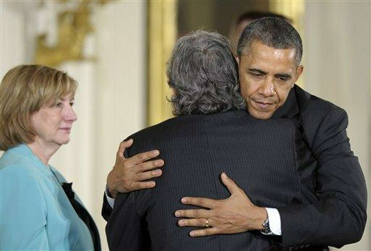 In this February 15, 2013, file photo President Barack Obama hugs Gilles Rousseau, father of slain Sandy Hook Elementary School teacher Lauren Rousseau, as her mother Terry Rousseau, watches at left during a White House ceremony in Washington to posthumously honor their daughter with the 2012 Presidential Citizens Medal. Families of the school shooting victims are making regular appearances with President Barack Obama and walking the halls of Congress to advocate for stricter gun regulations. They helped push through the nation's most restrictive firearms law in Connecticut this April. (AP Photo/Susan Walsh)