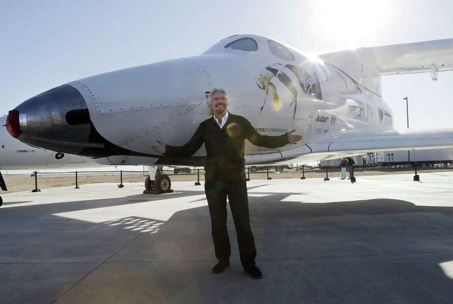 """FILE - In this Sept. 25, 2013, file photo, British entrepreneur Richard Branson poses with SpaceShipTwo at a Virgin Galactic hangar at Mojave Air and Space Port in Mojave, Calif. The Virgin Galactic's SpaceShipTwo space tourism rocket exploded Friday, Oct. 31, 2014, during a test flight, killing a pilot aboard and seriously injuring another while scattering wreckage in Southern California's Mojave Desert, witnesses and officials said. Virgin Galactic would not say what happened other than that it was working with authorities to determine the cause of the """"accident."""" (AP Photo/Reed Saxon, File) Photo: AP / AP"""