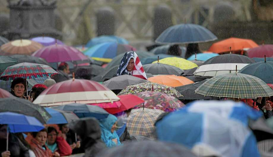 A person uses a U.S flag takes to shelter from the rain as he or she waits for the arrival Pope Francis for his weekly general audience Wednesday in St. Peter's Square at the Vatican. Photo: (AP Photo/Alessandra Tarantino) / AP