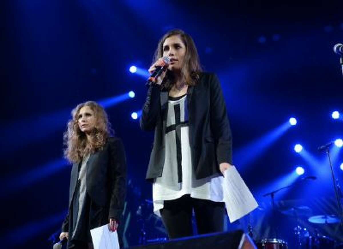 """Members of Pussy Riot, Maria Alekhina, left, and Nadya Tolokonnikova speak at Amnesty International's """"Bringing Human Rights Home"""" Concert at the Barclays Center on Wednesday, Feb. 5, 2014 in New York."""