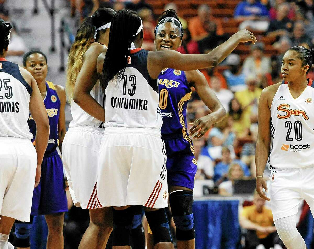 Sisters Connecticut Sunís Chiney Ogwumike, left, and Los Angeles Sparksí Nneka Ogwumike, right center, embrace at the start of a WNBA basketball game between the two teams, Sunday, July 13, 2014, in Uncasville, Conn. The two No. 1 picks in the WNBA draft are squaring off for the first time as pros. (AP Photo/Jessica Hill)