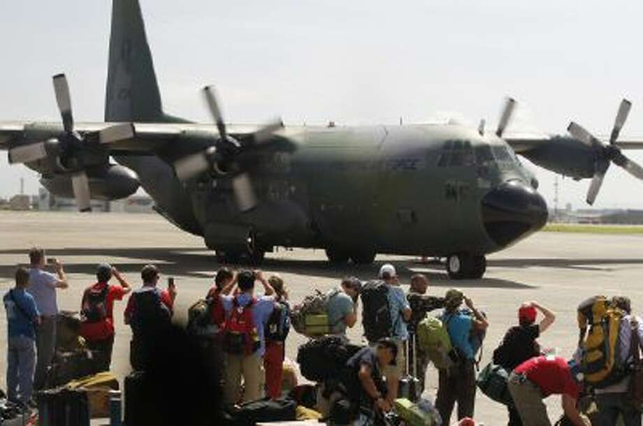 Local and foreign medical teams prepare to board a Philippines air force C-130 transport plane in Manila, Philippines on Sunday,