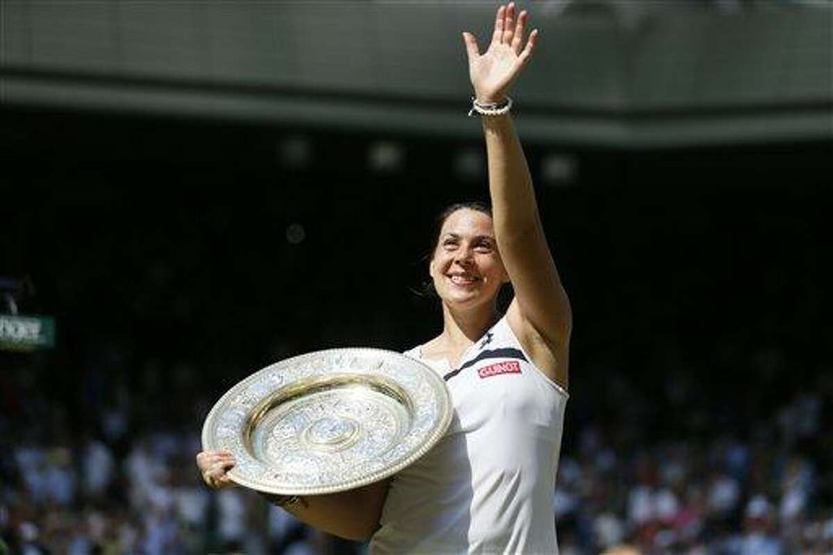 Marion Bartoli of France poses with the trophy after winning against Sabine Lisicki of Germany in the Women's singles final match at the All England Lawn Tennis Championships in Wimbledon, London, Saturday, July 6, 2013. (AP Photo/Stefan Wermuth, Pool)