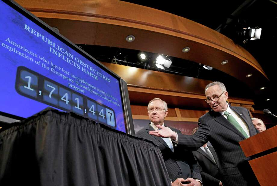 Sen. Charles Schumer, D-N.Y., the Democratic Policy Committee chairman, right, accompanied by Senate Majority Leader Harry Reid of Nev., points to a graphic during a news conference on Capitol Hill in Washington, Thursday, Feb. 6, 2014, where they told reporters that Republicans are thwarting Democratic efforts pass a bill to extend unemployment benefits which expired at the end of last year.  (AP Photo/J. Scott Applewhite) Photo: AP / AP