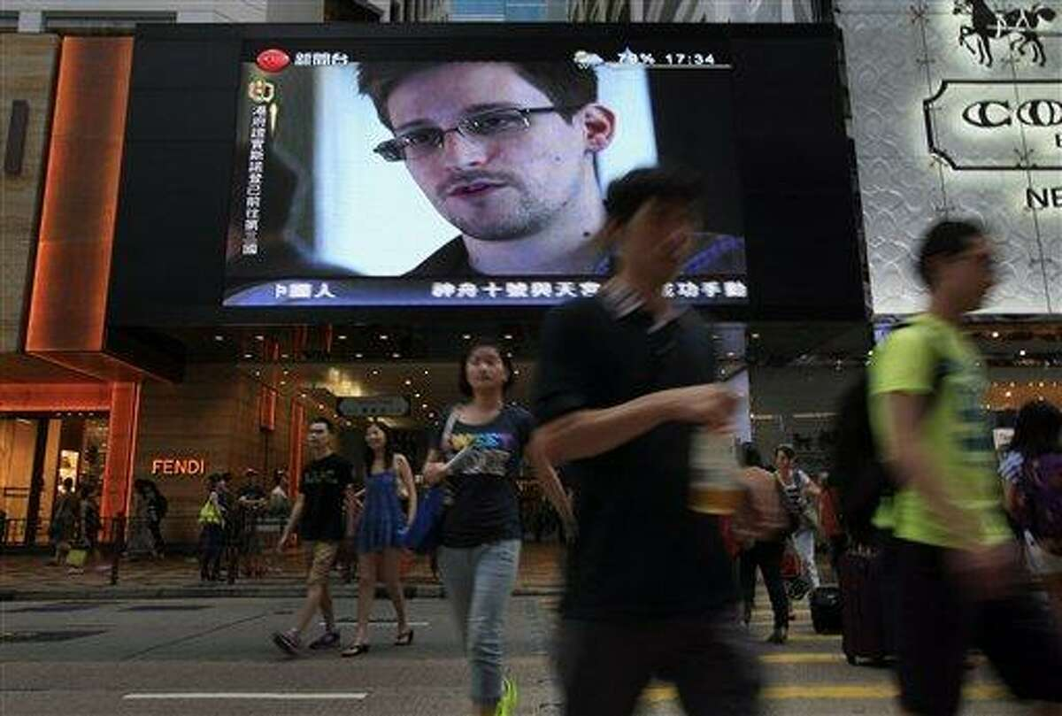 FILE - This June 23, 2013 file photo shows a TV screen shows a news report of Edward Snowden, a former CIA employee who leaked top-secret documents about sweeping U.S. surveillance programs, at a shopping mall in Hong Kong. President Barack Obama brushed aside sharp European criticism on Monday, suggesting all nations spy on each other, as the French and Germans expressed outrage over alleged U.S. eavesdropping on European Union diplomats. American analyst-turned-leaker Edward Snowden, believed to be stranded for the past week at Moscow's international airport, applied for political asylum to remain in Russia. (AP Photo/Vincent Yu, File)