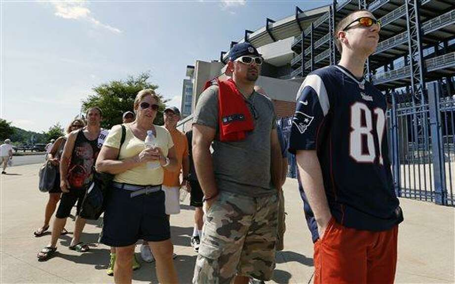Mike Davies, right, of Norfolk, Mass., wears his New England Patriots Aaron Hernandez football jersey one last time while waiting in an exchange line outside Gillette Stadium in Foxborough, Mass., Saturday, July 6, 2013. Fans may trade an Aaron Hernandez jersey with his name on it they purchased for one of another player on the NFL team. The team released Hernandez after he was arrested for allegedly orchestrating the death of Odin Lloyd. (AP Photo/Michael Dwyer) Photo: AP / AP