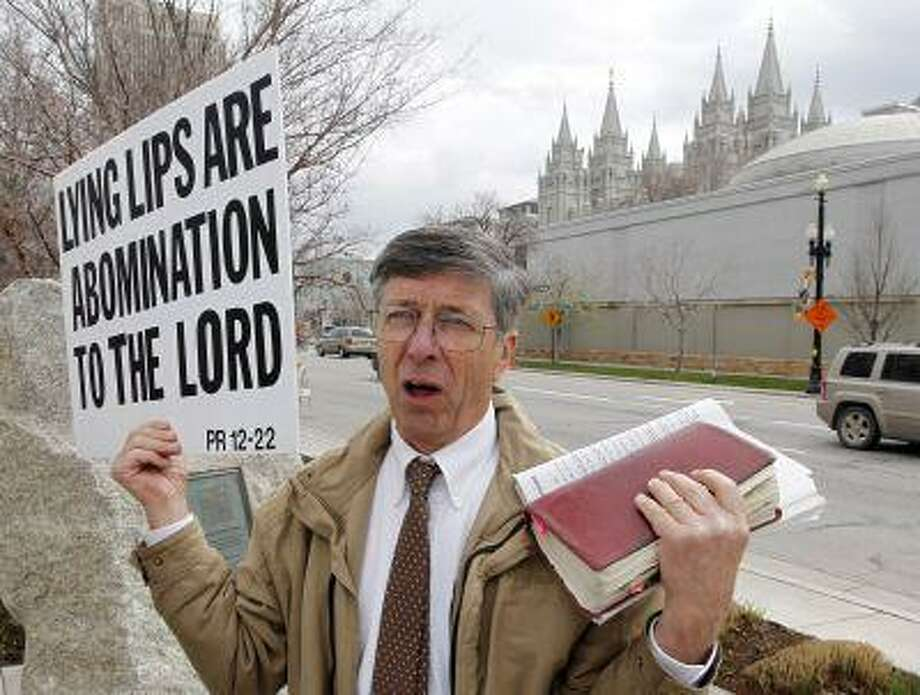A unidentified man who called himself Brother Carl carries a sign outside the Conference Center during the 183rd Annual General Conference of The Church of Jesus Christ of Latter-day Saints Saturday, April 6, 2013, in Salt Lake City. More than 100,000 members of the church have gathered in Salt Lake City to hear words of inspiration and guidance for daily living from the faith's senior leaders. (AP Photo/Rick Bowmer) Photo: AP / AP