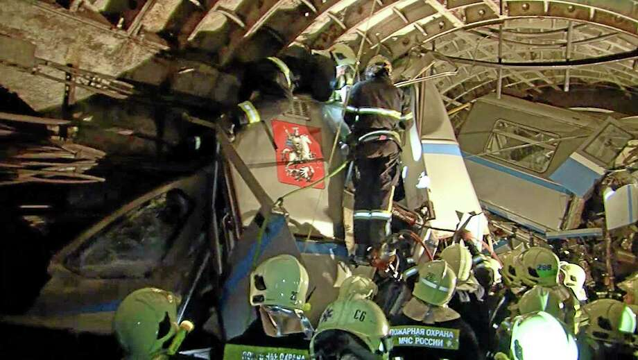 In this frame grab provided by the Russian Ministry for Emergency Situations shows frame grab from a video showing rescue teams working inside the tunnel where several cars of the wrecked train look almost coiled, occupying the entire space of the tunnel of Moscow subway in Moscow, Russia, on Tuesday, July 15, 2014. Workers were seen trying to force open the mangled doors of the car where dead bodies are supposed to be. A rush-hour subway train derailed in Moscow Tuesday, killing about a dozen people and injuring at least 150, emergency officials said. Several cars left the track in the tunnel after a power surge triggered an alarm, which caused the train to stop abruptly. (AP Photo/Russian Emergency Situation Ministry) Photo: AP / Russian Emergency Situation Ministry
