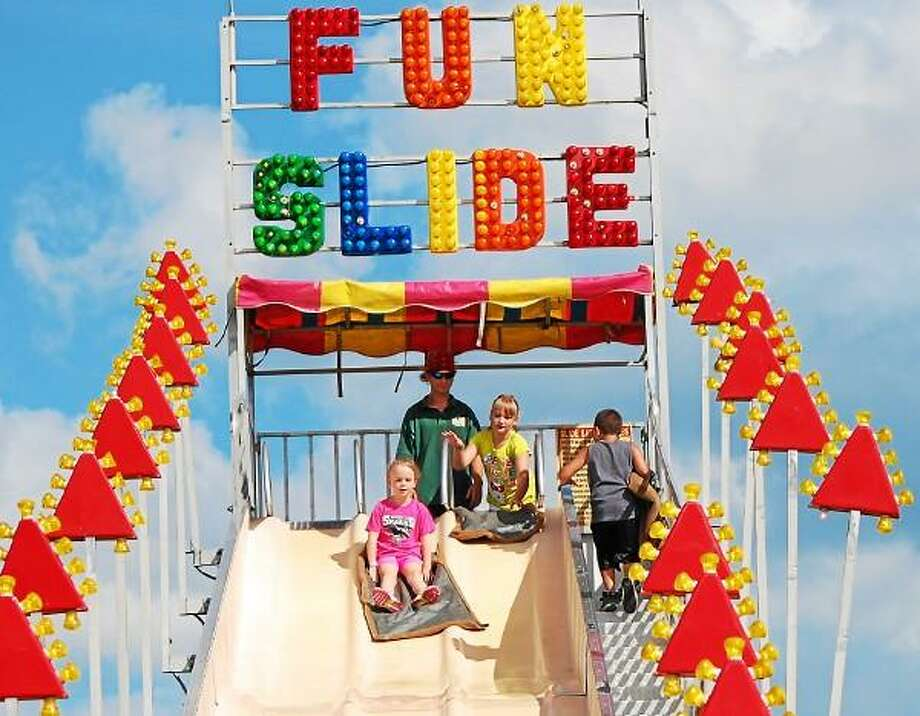 Brooke Fallon, left, heads down the Fun Slide, followed by her sister, Emma, center, during the Independence Day carnival at Torrington Middle School on July 6. (Tom Caprood-Register Citizen)