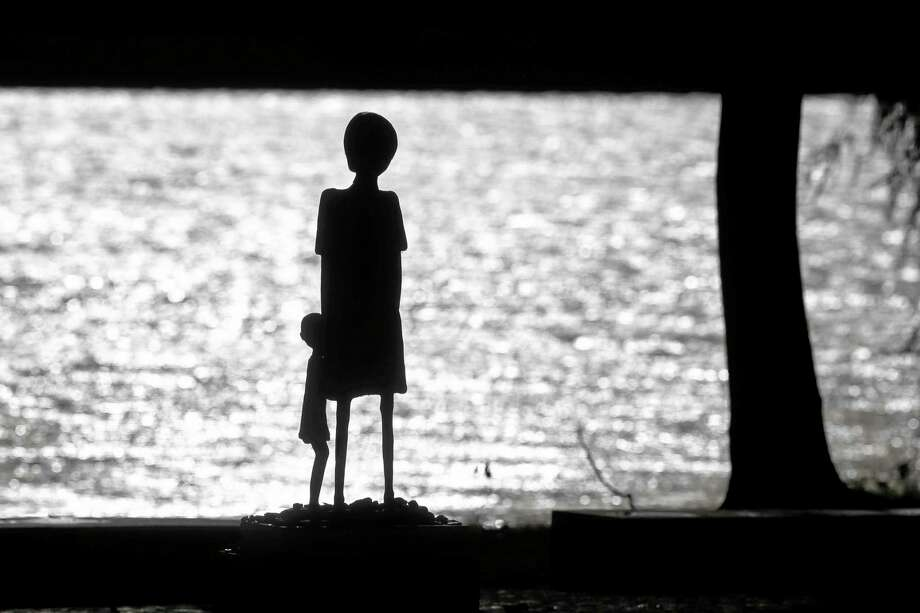 A sculpture of a woman and a child is silhouetted against the water of Schwedsee lake at Nazi death camp Ravensbrueck about 100 kilometers (62 miles) north of Berlin, Thursday, Nov. 7, 2013. On Nov. 9, 2013 Germany remembers the 75th anniversary of the 'Kristallnacht', 'Night Of The Broken Glasses' or 'November Pogrom'. On Nov. 9, 1939  the Nazis coordinated a wave of attacks in Germany and Austria, smashing windows, burning synagogues, ransacking homes and looting Jewish-owned stores. (AP Photo/Markus Schreiber) Photo: AP / AP