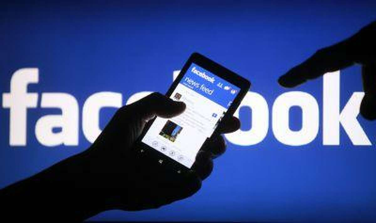 A smartphone user shows the Facebook application on his phone in the central Bosnian town of Zenica, in this photo illustration taken May 2, 2013. REUTERS/Dado Ruvic/Files