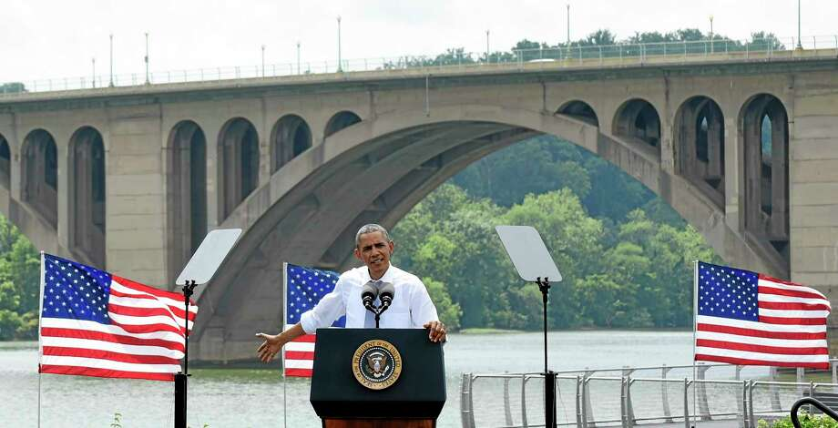 With the Key Bridge, linking Washington and Northern Virginia in the background, President Barack Obama speaks about the economy and transportation, Tuesday, July 1, 2014, at Georgetown Waterfront Park in Washington. The president said 700,000 jobs could be at risk next year if Congress doesn't quickly agree on how to pay for highway and transit programs.  (AP Photo/Susan Walsh) Photo: AP / AP