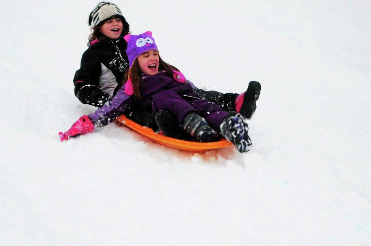 Sarah Flynn, 11, and Sadie Zalewski, 7, both of Branford, sled behind Branford Town Hall Wednesday.