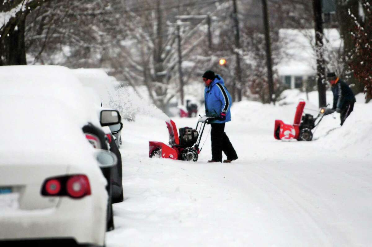 Mark Kirschner removes heavy snow from driveway on Wilford Avenue in Branford Wednesday morning.