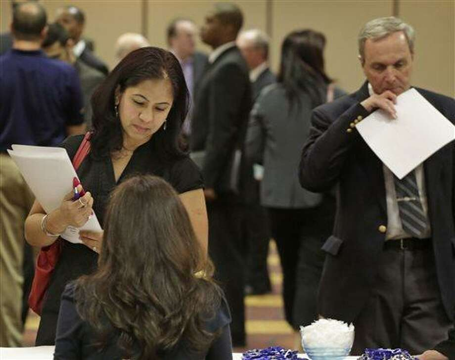 In this May 29, 2013 photo, job seeker Anu Vatal of Chicago, speaks with Patrice Tosi of BluePay, seated, during a career fair in Rolling Meadows, Ill. The U.S. economy added 175,000 jobs in May, a gain that shows employers are hiring at a still-modest but steady pace despite government spending cuts and higher taxes, according to the Labor Department, Friday, June 7, 2013. (AP Photo/M. Spencer Green) Photo: ASSOCIATED PRESS / AP2013