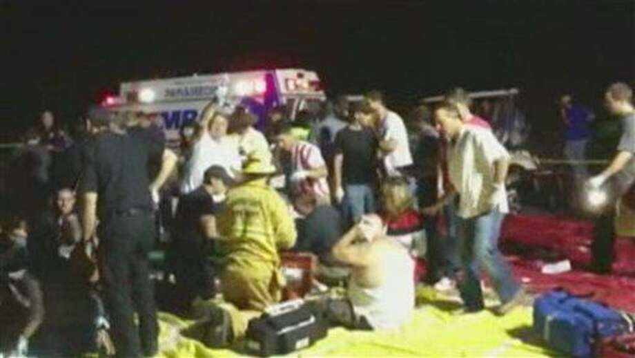 In this frame grab from video provided by Zach Reister, authenticated by checking against known locations and events, and consistent with Associated Press reporting, medical personnel attend the injured after a fireworks show in Simi Valley, Calif., Thursday, July 4, 2013. More than two dozen people were injured when a wood platform holding live fireworks tipped over, sending the pyrotechnics into the crowd at the Fourth of July show, authorities said Friday. (AP Photo/Zach Reister) Photo: AP / Zach Reister